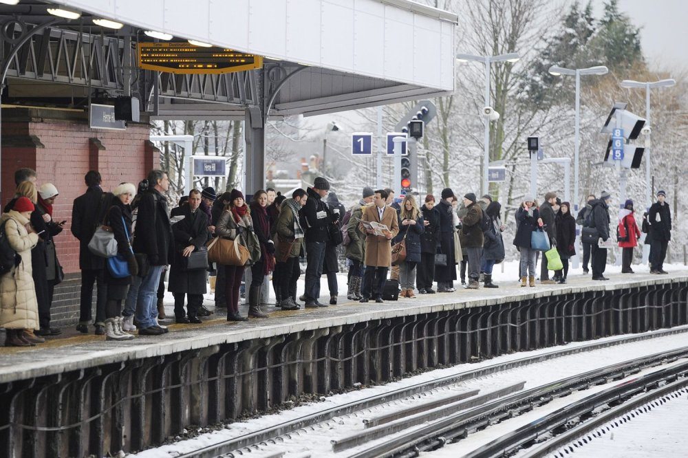 A long queue of passengers waiting for a train to come, under heavy snow